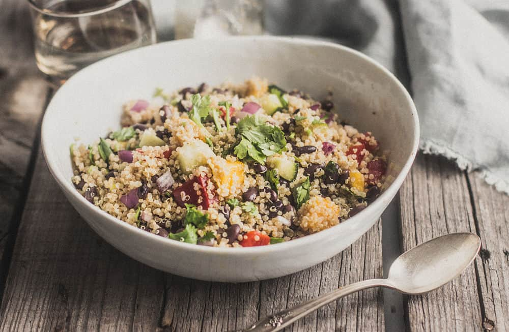 Quinoa, mango, and black bean salad in a white bowl