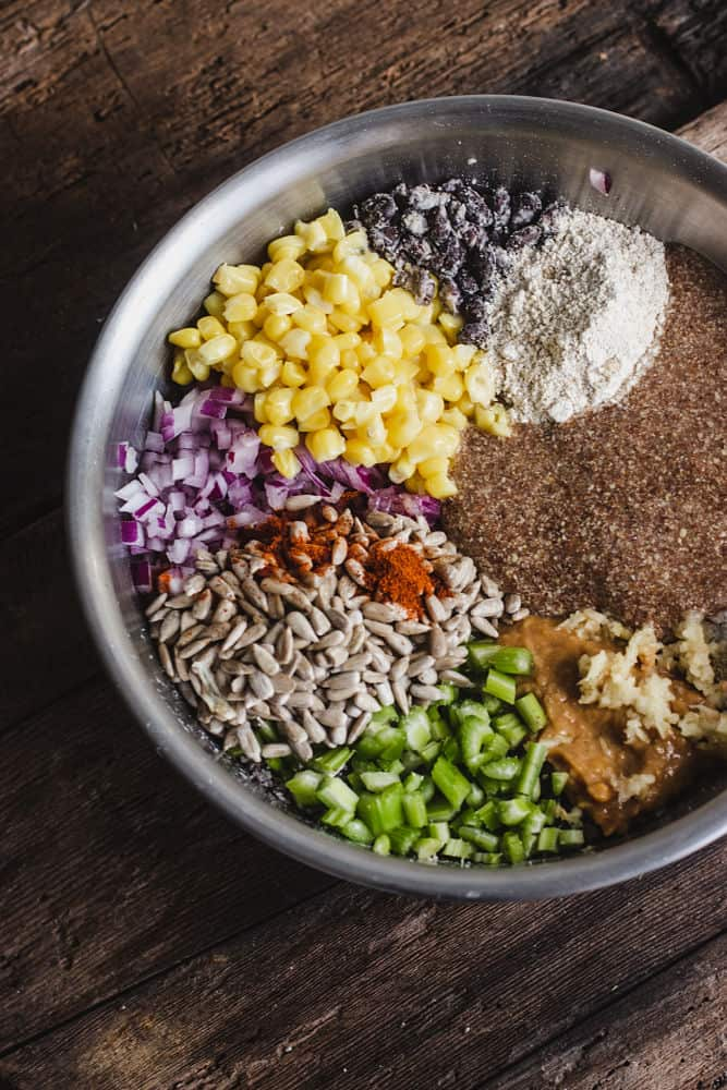 Ingredients in sections in a bowl: smashed cooked blacks beans, corn, diced red onions, Cayenne pepper on top of sunflower seeds, chopped celery, crushed garlic on top of miso loose paste, ground meal and oar flour