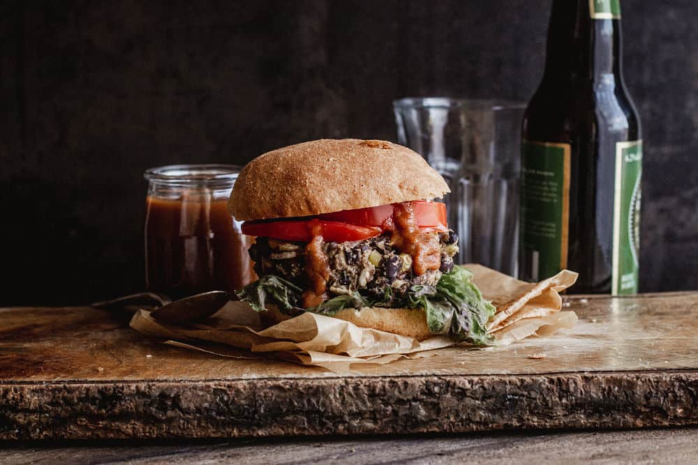 A burger on a narrow wooden board with ketchup oozing our of it in front of a small jar of bbq sauce, an empty glass and a beer