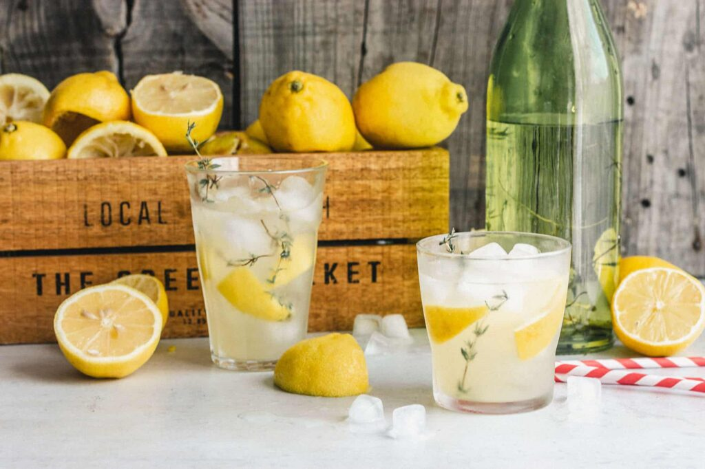 Two glasses of lemonade in front of a small wood container of lemons