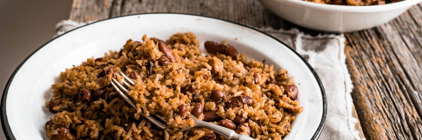 Dark rice in an enamel plate with a fork in it
