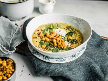 Spiced Chickpea Stew with Curry and Coconut in a white bowl on top of a blue jean napkin