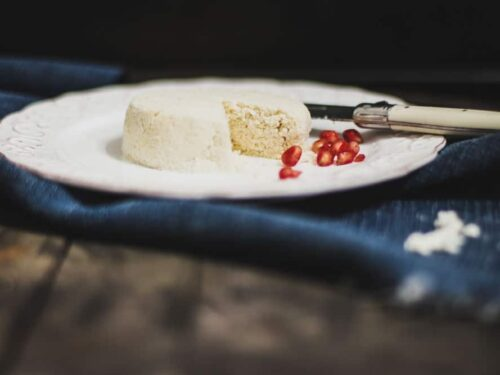 Cheese-looking round food with a on a salad plate with pomegranate arils next to it