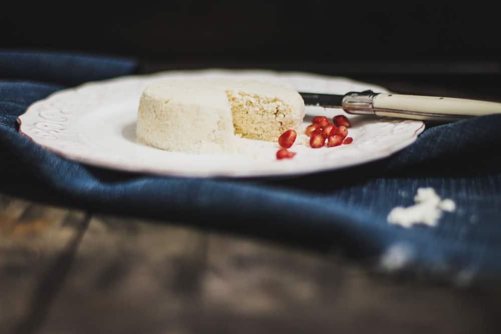 Nourriture ronde à l'aspect de fromage avec sur une assiette à salade avec des graines de grenade à côté