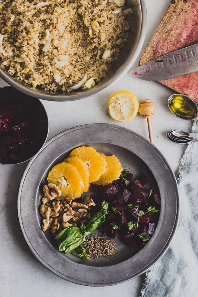 Top view of quinoa salad with beets, and walnuts. Clockwise: sliced oranges, cubed cooked beets, cumin seeds, basil leaves, walnuts on a metallic plate