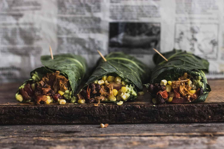Burritos au jacquier effiloché enveloppé dans une feuille de chou vert allongé sur une fine planche à découper en bois avec du papier journal en arrière-plan