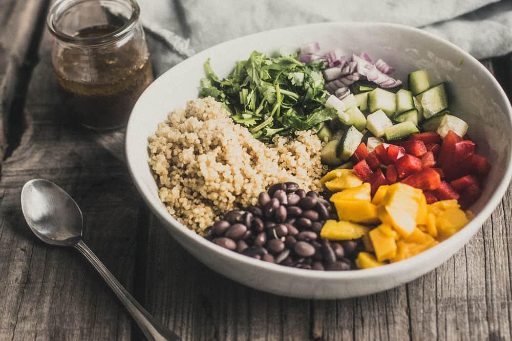 Ingrédients pour salade de quinoa à la mangue et aux haricots noirs placés en sections dans un bol blanc. De gauche à droite dans le sens des aiguilles d'une montre : quinoa cuit, coriandre, oignons rouges en dés, concombre en dés, mangue en dés, haricots noirs cuits