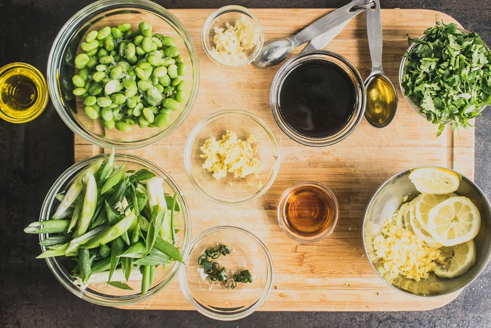 Bird's eye view of ingredients in small glass bowls on a wooden cutting boar. From left to right, clockwise: olive oil, edamame, crushed garlic, tamari, sesame oil in measuring spoon, cilantro, limes slices and zest, mirin, grated ginger, and green onions cut in long pieces,
