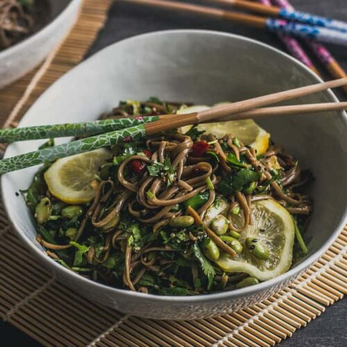 Soba noodle, edamame, sliced lemon in a white bowl with two chopsticks over the bowl