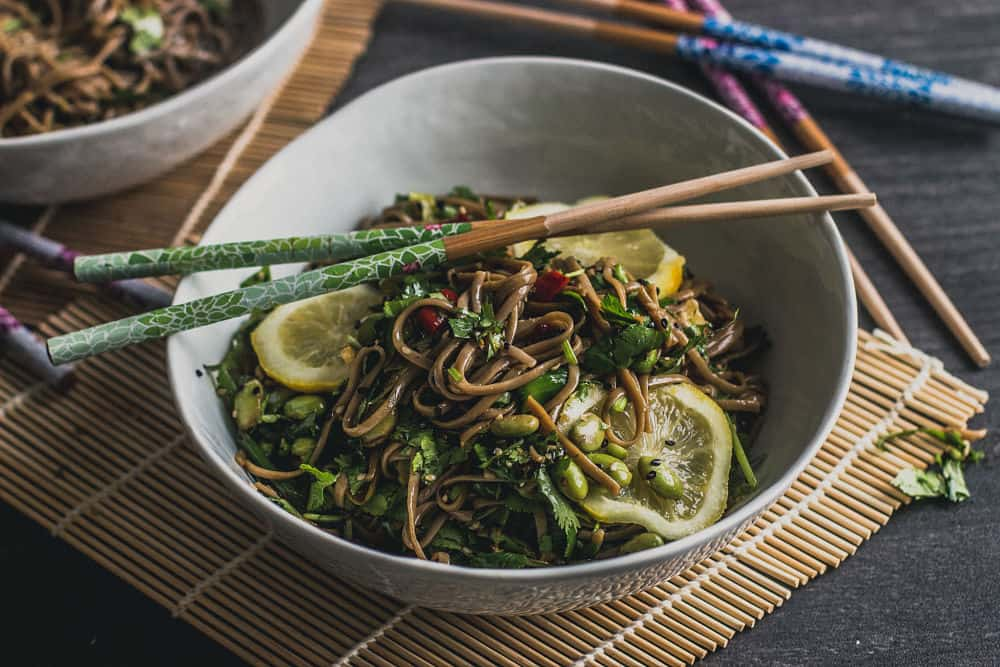 Soba noodles with lemon slices and edemame in white bowl with Asian sticks on top