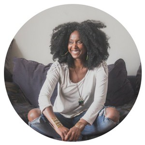 Smiling girl with big afro sitting cross-legged on a sofa