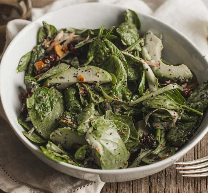 Spinach salad with sliced avocado and cranberry with poppy seeds vinaigrette