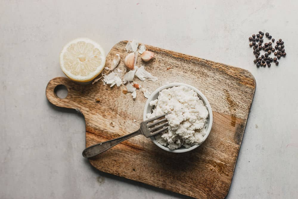 Bird's eye view of a ricotta style cheese in a ramekin on top of a small wooden cutting board