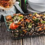 Lentil, barley, and sweet potato salad with broccoli and baby tomatoes in a glass baking dish sitting on a wooden board