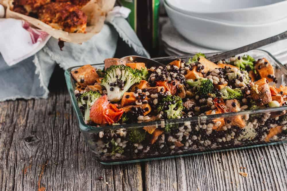 Salade de lentilles, d'orge perlée et de patate douce dans un plat au four et entouré d'assiettes et  de bols superposés