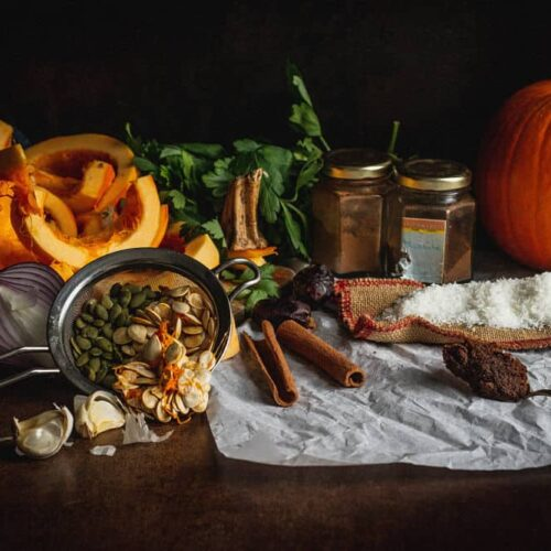 Still life (clockwise or left to right: pumpkin cut in half, parsley, two small jars of cinnamon and nutmeg, whole pumpkin, coconut flakes resting on small bag jute, miso in a spoon, cinnamon sticks, Medjool dates, green and yellow pumpkin seeds in a small sieve, garlic cloves, red onion cut in half