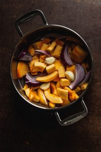 Overhead view of pieces of pumpkin, onion, and garlic in a pot for steaming