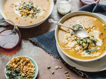Overhead view of two bowls of pumpkin soup placed diagonally with a glass of red wine in the left corner and roasted pumpkin and squash seeds on a small plate