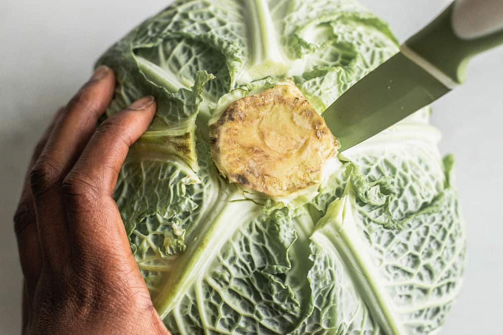 Bird's eye view of a dark-skinned hand holding a cabbage turned upside down with vegetable knife stabbed inside
