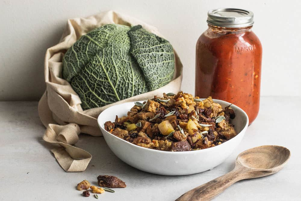Savoy cabbage in a cloth bag with a white bowl of stuffing and a medium jar of tomato sauce