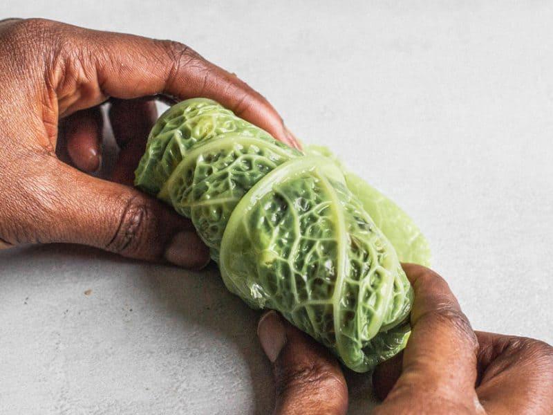 Dark-skinned hands rolling a Savoy cabbage leaf
