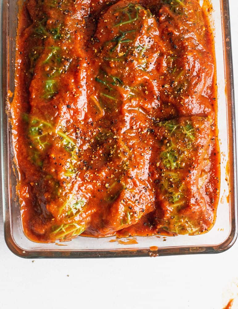 Bird's eye view of casserole dish with stuffed cabbage rolls topped with tomato sauce