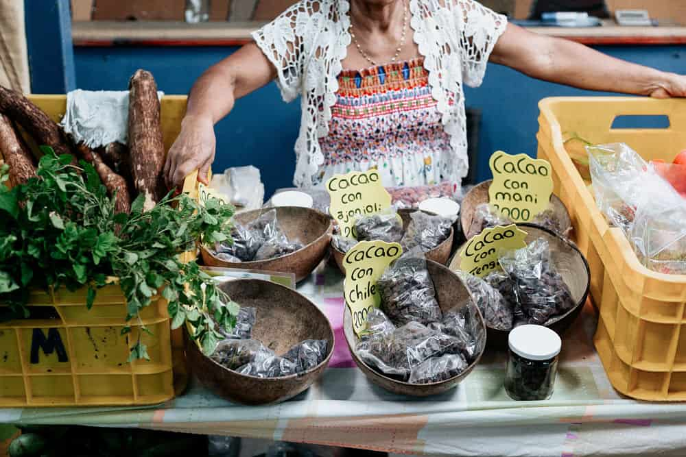 Baskets of small bags of cacao between two yellow with an old lady standing behind the stand