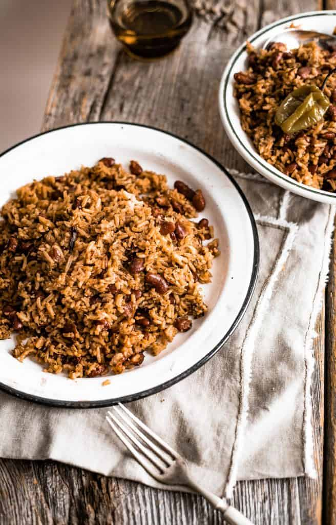 Two plates of Caribbean Rice and Beans on white plates on a wooden board