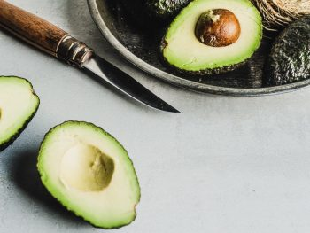 Avocado cut in half next to a metallic plate of cut and whole avocadoes