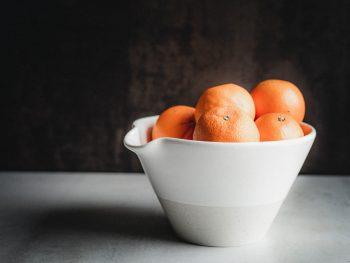 Oranges in a rustic ceramic bowl