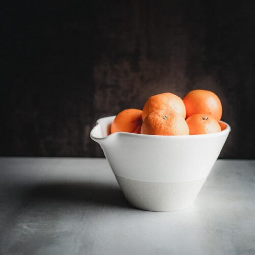 Oranges in a rustic ceramic bowl