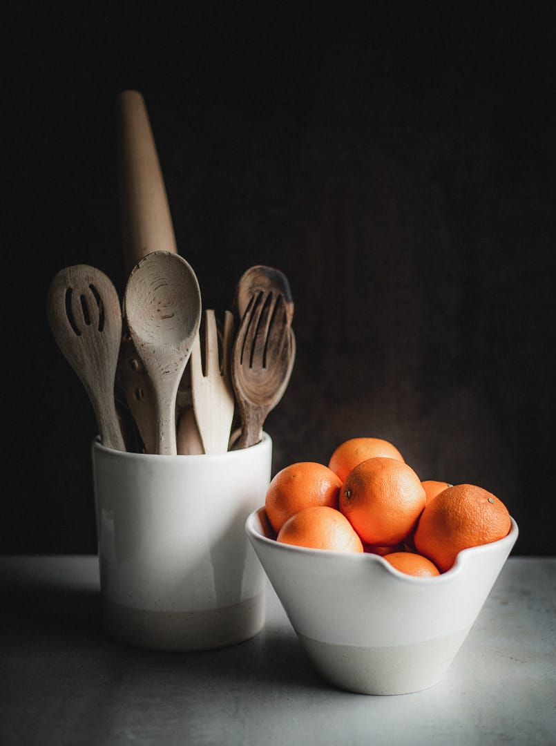 Wooden spoons and forks in a big two-toned (white and sand) ceramic canister next to a matching mixing bowl with oranges in it