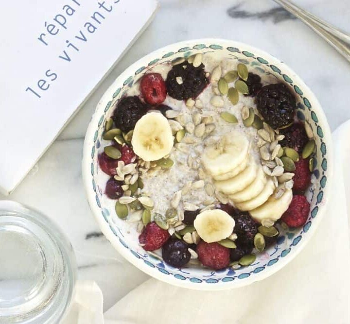 Chia pudding with sliced bananas, berries, pumpkin seeds and sunflower seeds in a colorful bowl