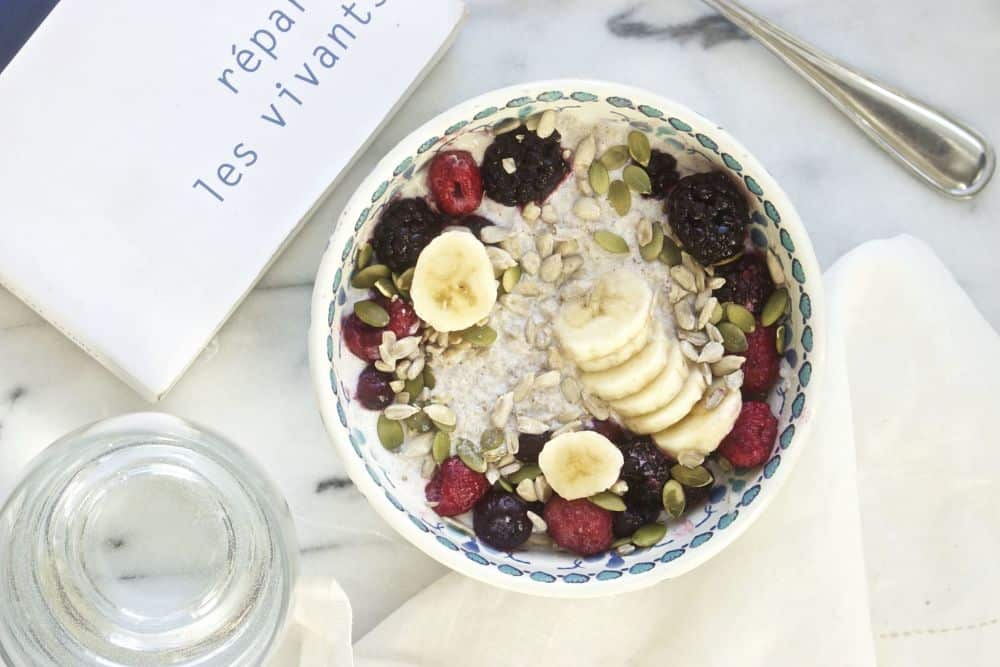 Top view of chia pudding with sliced bananas, berries, pumpkin seeds and sunflower seeds in a colorful bowl