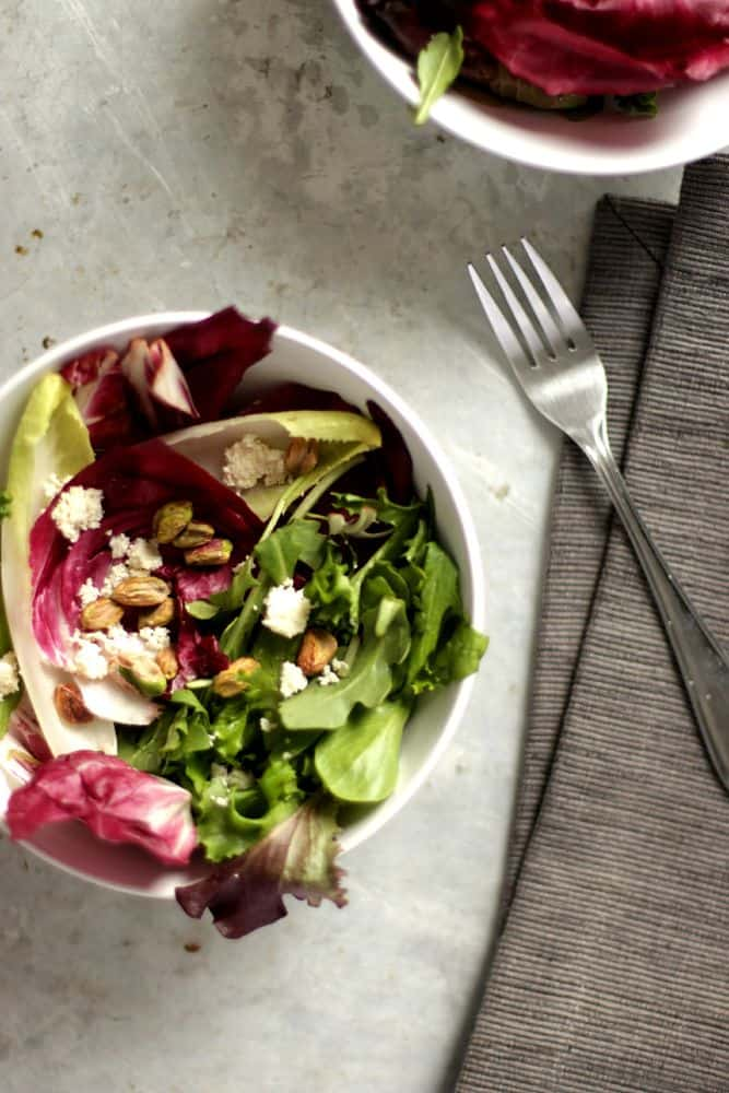 Top view of two bols of radicchio and endive salad with pistachios and almond ricotta