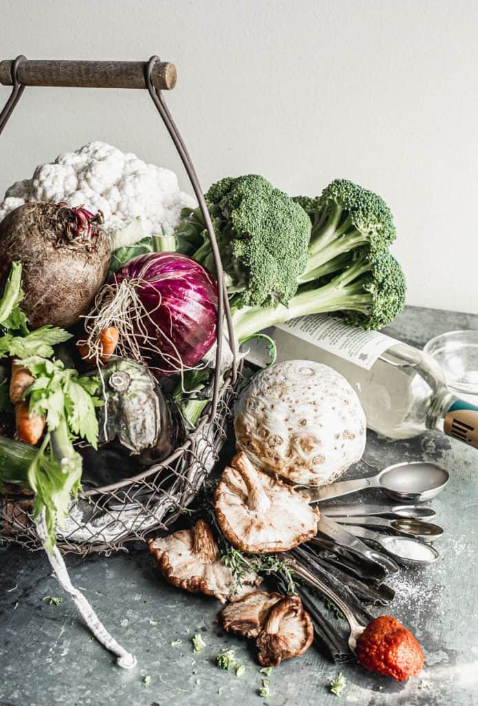 vegetables overflowing from a rustic wire basket with beside it, a bottle of wine lying down, a set of measuring spoons filled with pectin, olive oil, salt, and tomato paste, on top whit celeriac, sprigs of thyme, and shiitake mushrooms on top