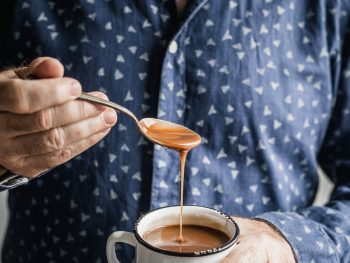 A man, dressed in a dark blue shirt, holds a spoon in his left hand and pours brown sauce into a white enamel mug that he's holding in his right hand]