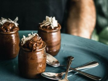 Chocolate mousse in three small jars with large coconut flakes on top on a plate being held by a man in the background