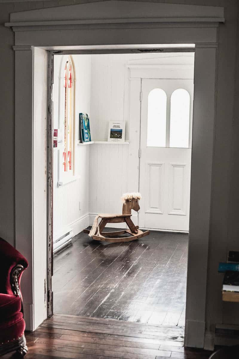 Chambre à l'Auberge Le 112, à St-André de Kamouraska, avec un cheval de bois dans le coin de la chambre sous un vitrail
