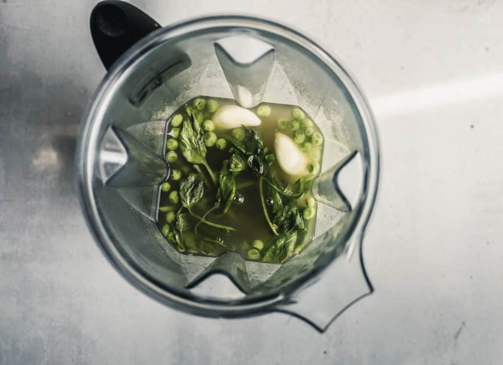 Overhead view of peas, garlic cloves, and basil on the surface of vegetable broth in a blender