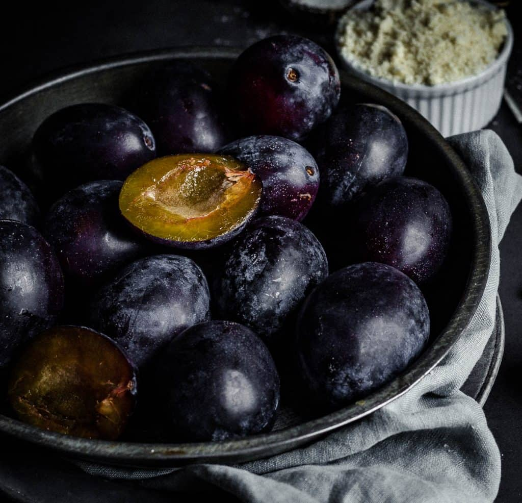 Plums cut in half in a metallic plate