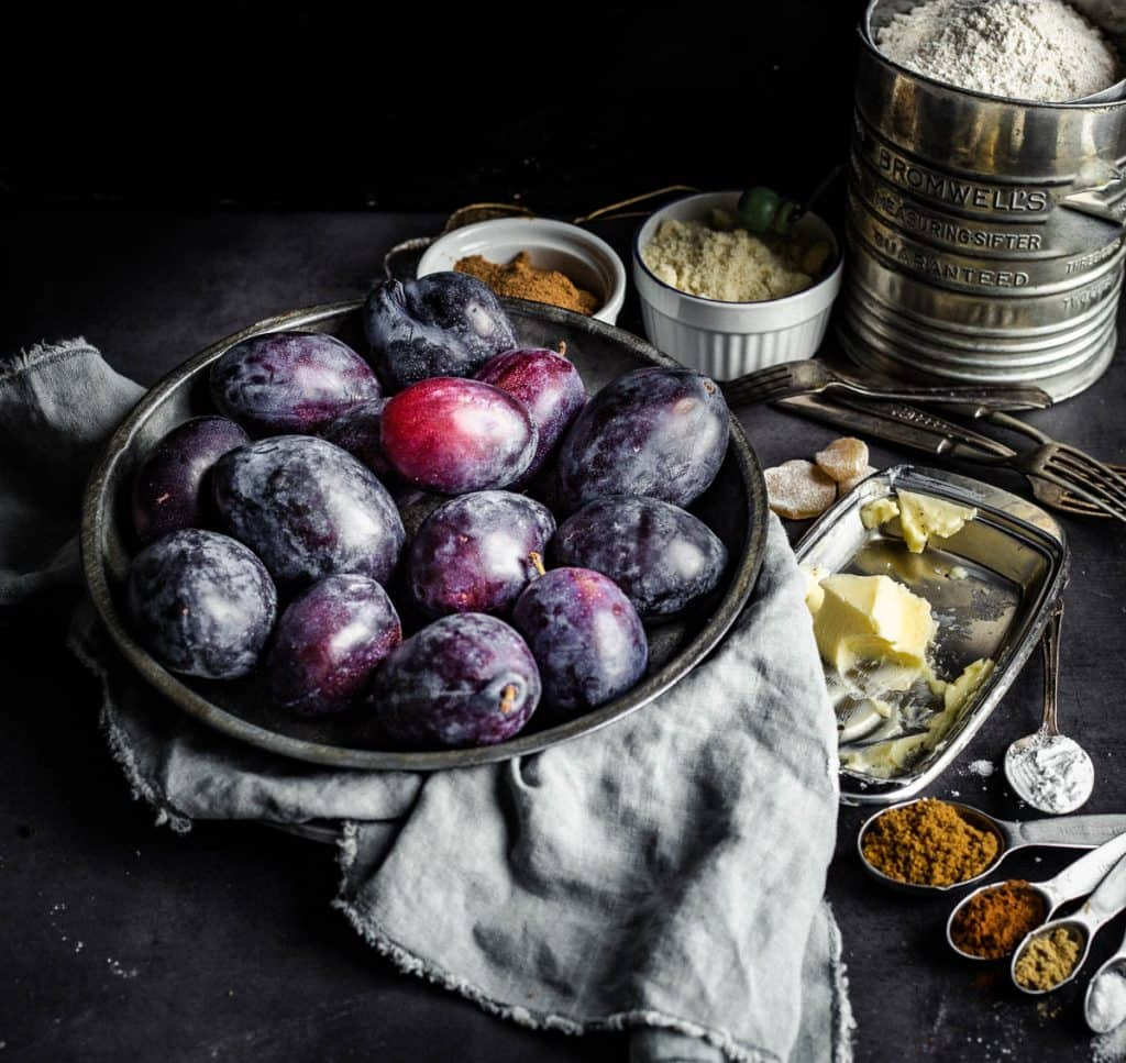 Oblong plums in a metallic plate surrounded by different types of flours in bowls, butter on a butter dish, and spices in measuring spoons