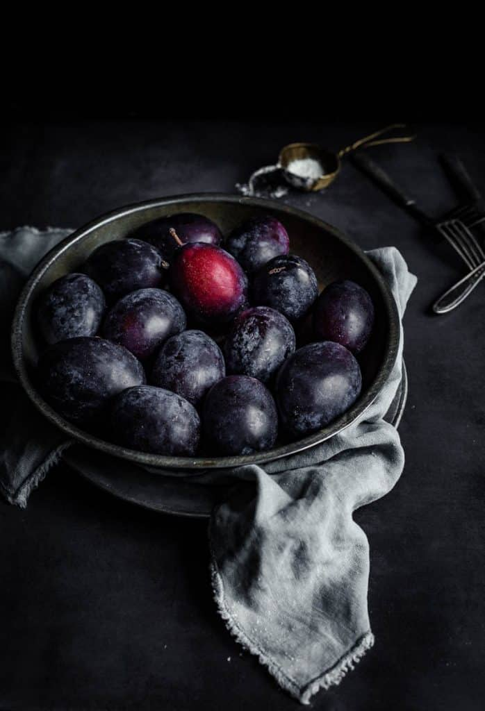 Oblong plums in a metallic plate in a dark background