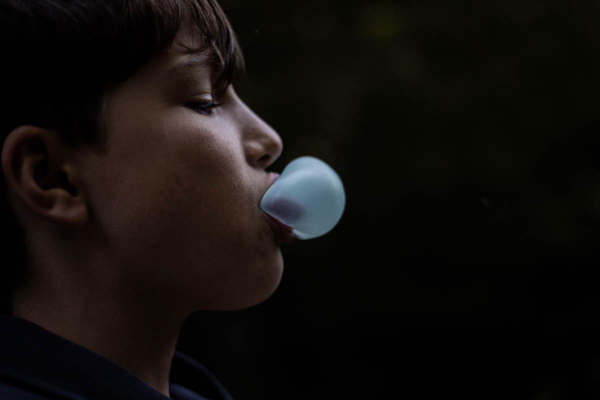 The profile of a little boy blowing blue bubble gum