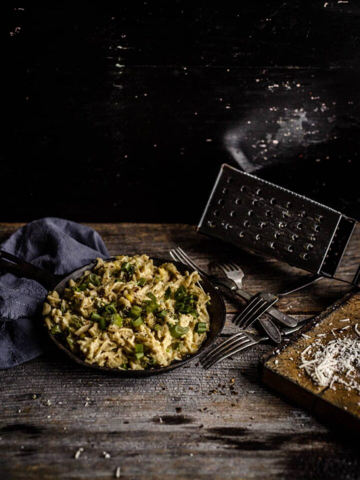 Creamy corn fusilli with green onions and basil in a cast-iron pan on a wooden board and other decorative items