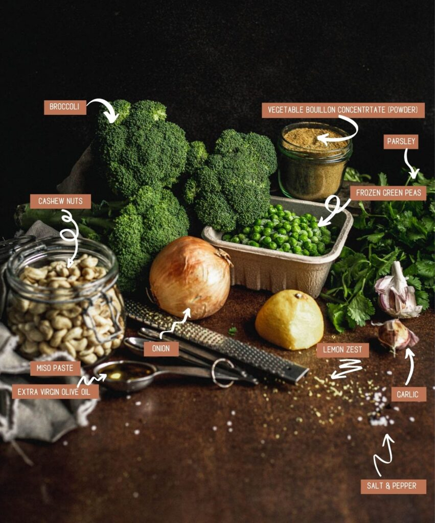 Ingredients for the broccoli and pea soup (clockwise): broccoli, peas in a small square container, powdered vegetable broth in a small glass jar, a bunch of parsley, cloves of garlic, half a lemon, lemon zest, onion, olive oil and miso in a set of spoons and cashews in a small mason jar