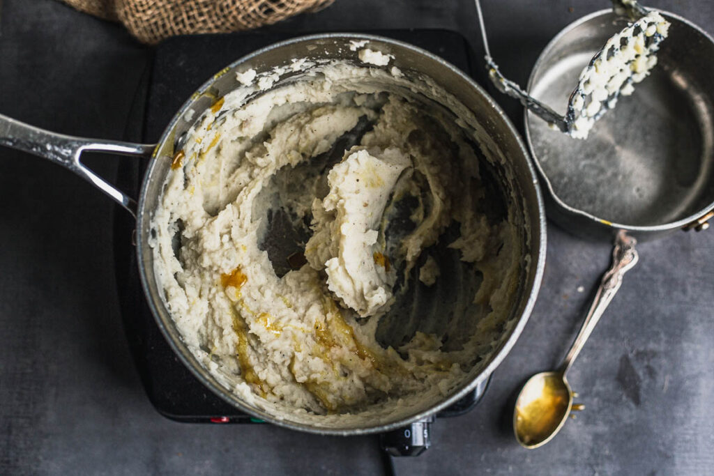 Mashed potatoes in saucepan with golden thick liquid squirted on
