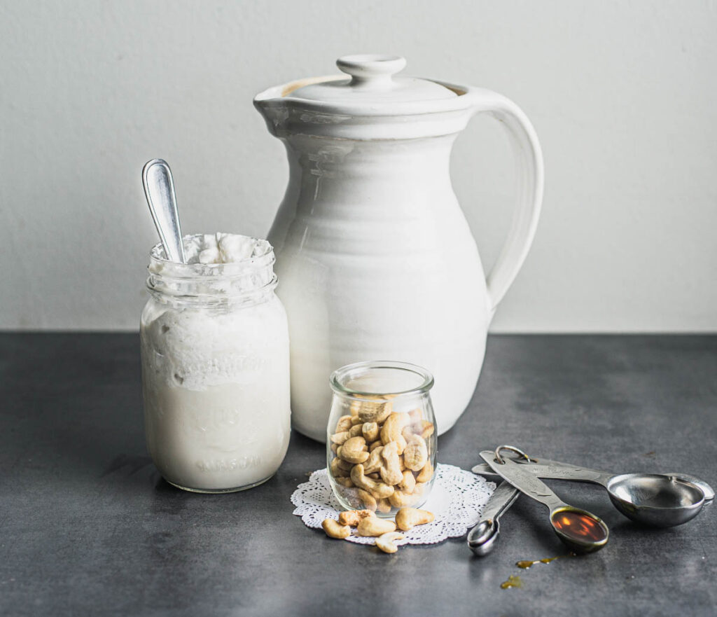 Ingredients for half-and-half (clockwise: coconut cream in a small Mason jar, ceramic jug, cashews in a small glass yogurt jar, set of measuring spoons