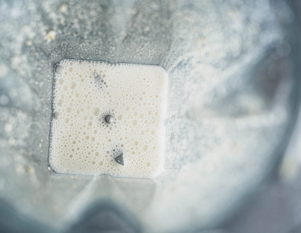 Overhead view of white milk-like liquid in blender pot