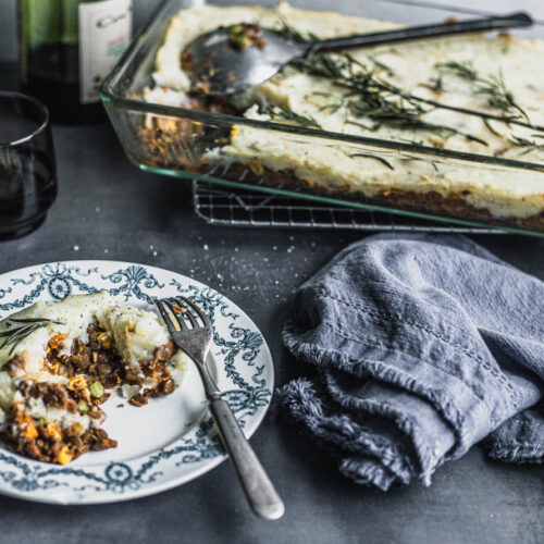 Piece of Cottage Pie style lentil pie in a small plate placed in front of a glass pan of the whole dish